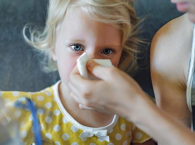 어린 소녀가 위생적인 물티슈로 코를 푸는 것을 돕는 부모의 손