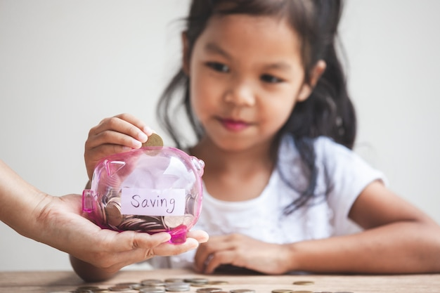 Parent hand holding piggy bank and cute asian child girl putting money into piggy bank