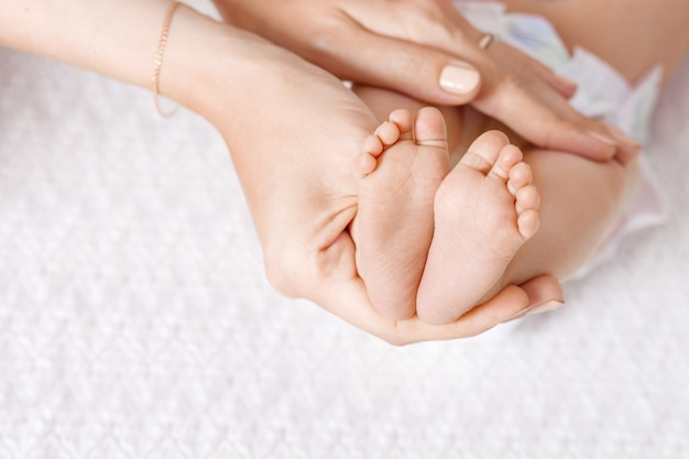 Parent holding in the hands feet of newborn baby. tiny newborn baby's feet on hands closeup.