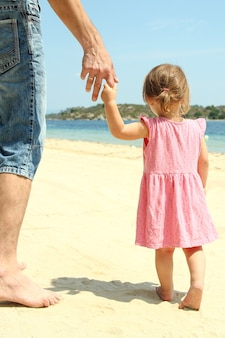 The parent holds the hand of a small child near the sea