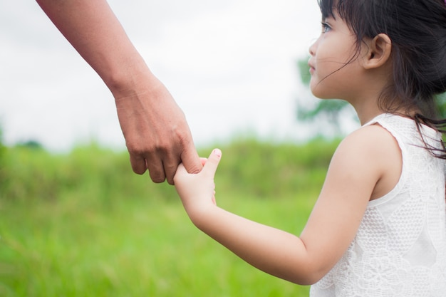 A parent holds the hand of a small child, outdoor nature