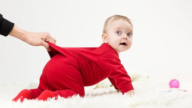 親は赤ちゃんの服を手で持って、遠くまではいられないようにします。