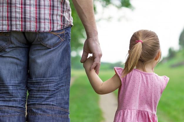 親は小さな子供の手を握って歩く