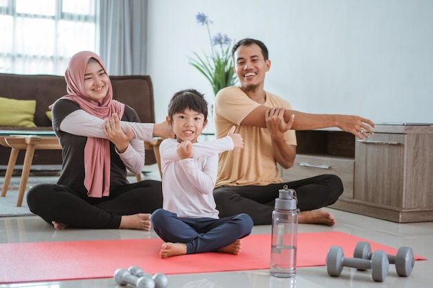 Parent and kid doing exercise together. portrait of healthy muslim family workout at home