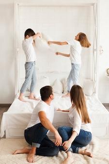Родитель смотрит на своих детей, борющихся на кровати дома