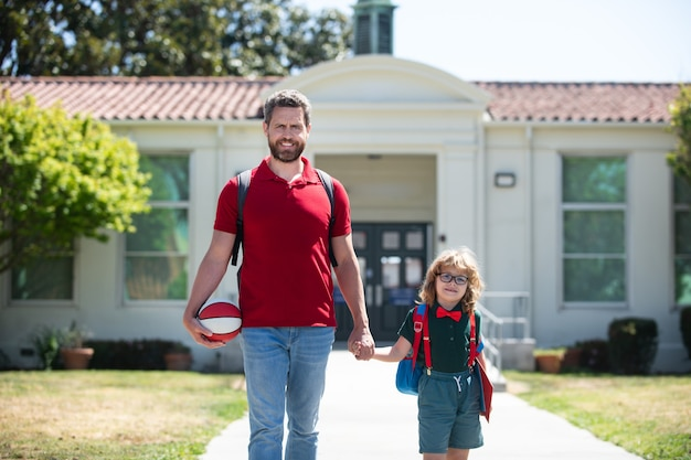 Parent and pupil of primary school go hand in hand. teacher in t-shirt and cute schoolboy with backpack near school park