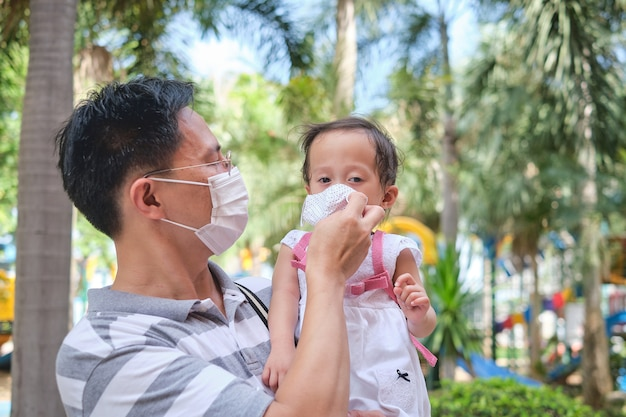 Parent putting mask on his asian toddler girl child, father and daughter wearing protective medical mask in public playground