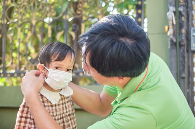 Parent putting mask on his asian toddler girl child