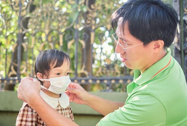 그의 아시아 유아 여자 아이에 마스크를 씌우고 부모