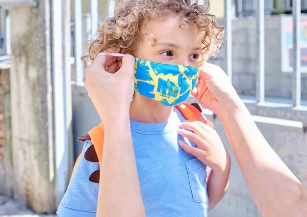 학교 입구에서 아이에게 보호용 안면 마스크를 씌우는 부모