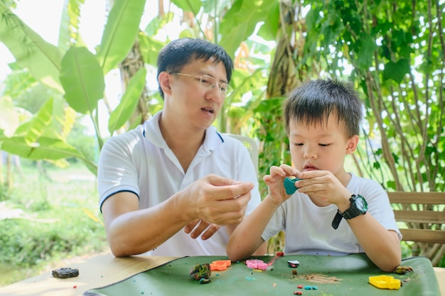 小さな子供と一緒にホームスクーリングに座っている親、カラフルなモデリング粘土を楽しんでいるアジアの父と息子、自然の裏庭の庭で生地を再生、自宅で学ぶ、楽しいホームスクールのコンセプト