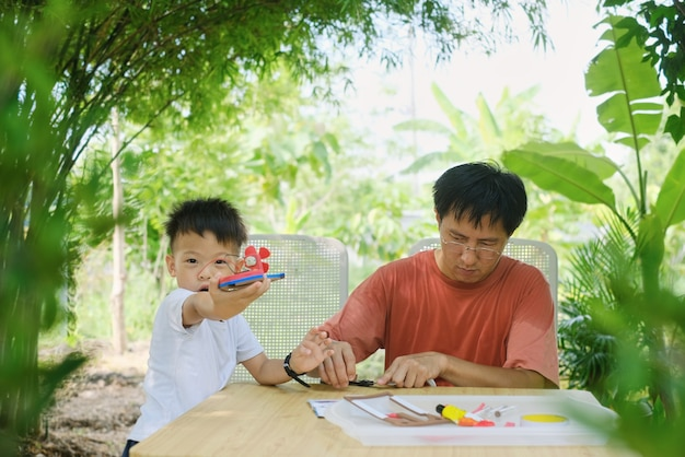 Parent sitting homeschooling with little kid asian father and son having fun making diy toy boats