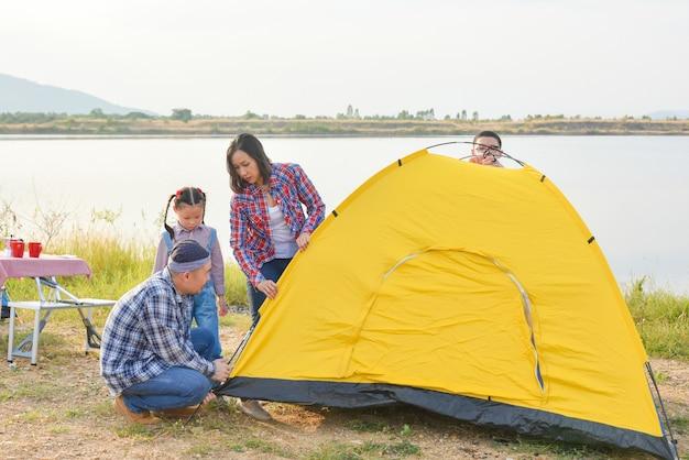 Родитель с детьми устанавливают палатку в кемпинге семейное приключение на свежем воздухе в отпуске