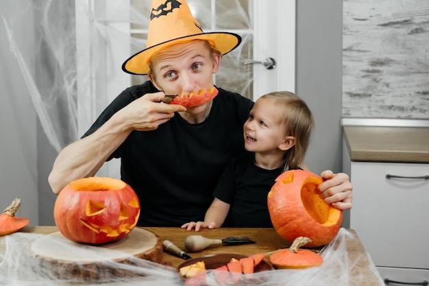 Родитель с ребенком вырезают тыкву на хэллоуин