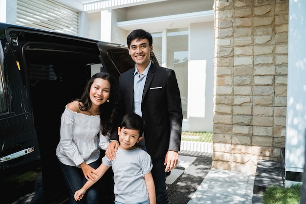 笑顔の車の前で子供を持つ親