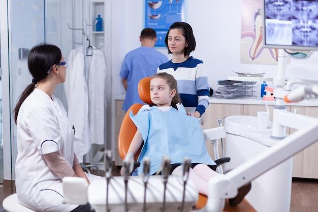 歯科医院で口の衛生について話している小児歯科医を聞いている小さな女の子を持つ親。歯の間に母親と一緒にいる子供は、椅子に座っている口内検査で診察します。