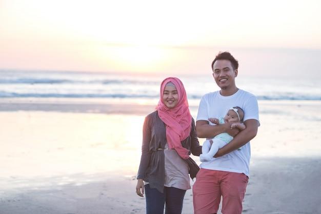一緒に楽しんでビーチで生まれたばかりの赤ちゃんを持つ親