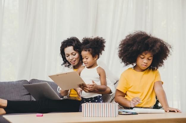 Covid-19 바이러스 전염병 질병의 건강한 어머니가 자녀와 함께 머물고 노는 행복한 삶의 인터넷 컴퓨터 노트북 효과로 집에서 일하는 부모