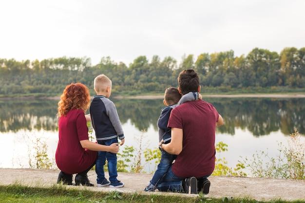 親子関係、子供時代、家族の概念-公園を歩いて何かを見ている親と2人の男性の子供、背面図