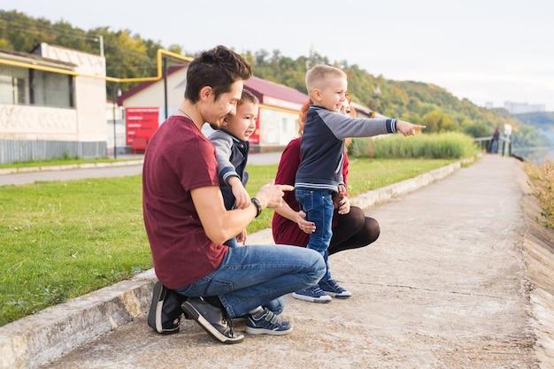 親、子供、家族の概念-公園を歩いて何かを見ている親と2人の男性の子供。