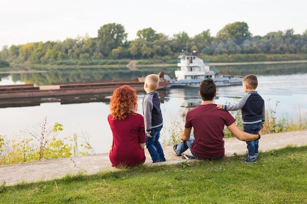 親子関係、子供時代、自然の概念-緑の地面に座って小さなボートを見ている家族。