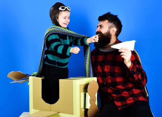Parenthood concept. happy son playing with father. dad and child plays with cardboard airplane. family having fun.