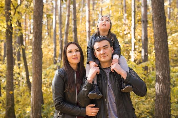 親子関係、秋、人々の概念-秋の公園で幸せな若い家族。