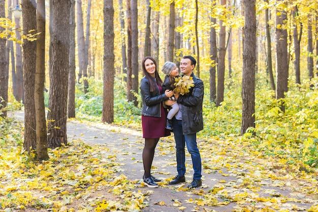 Концепция отцовства, падения и людей - молодая семья счастлива в осеннем парке.