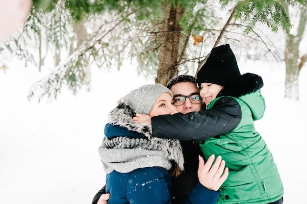 親子関係、ファッション、人々の概念-公園で屋外を歩く冬服の幸せな家族。