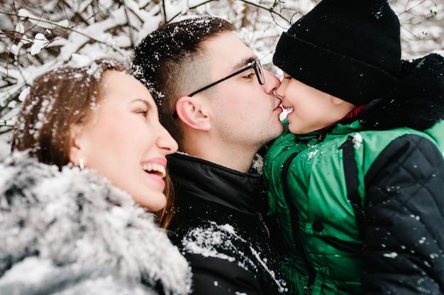 親子関係、ファッション、季節、人々の概念-公園で屋外を歩く冬服を着た子供と幸せな家族。メリークリスマスを祝うというコンセプト。
