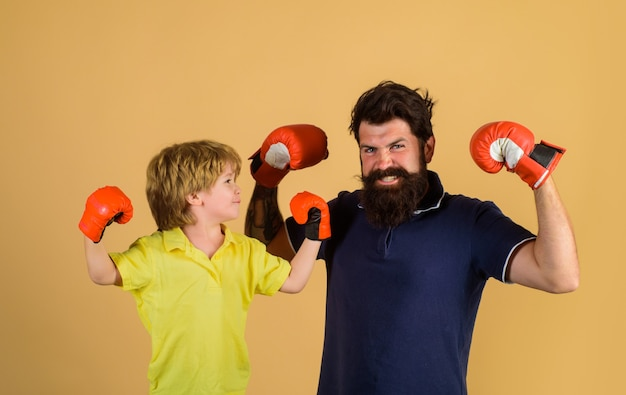 Parenthood relationship ready for sparring bearded sports man coaching boxing little boy in red