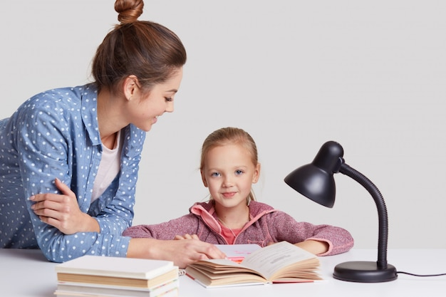 Parenthood, studying and education concept, blue eyed female child sits at workplace, reads book together with mother, learns poem by heart, pose in cozy room on white