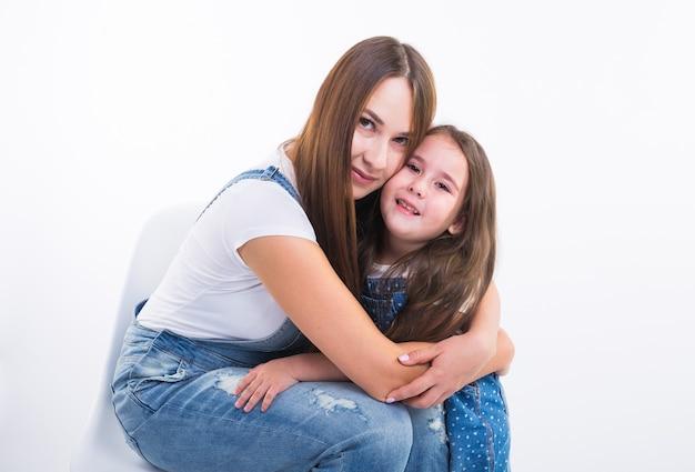 Концепция воспитания, семьи и детей - портрет матери и ее девочки весело и улыбается над белой стеной.