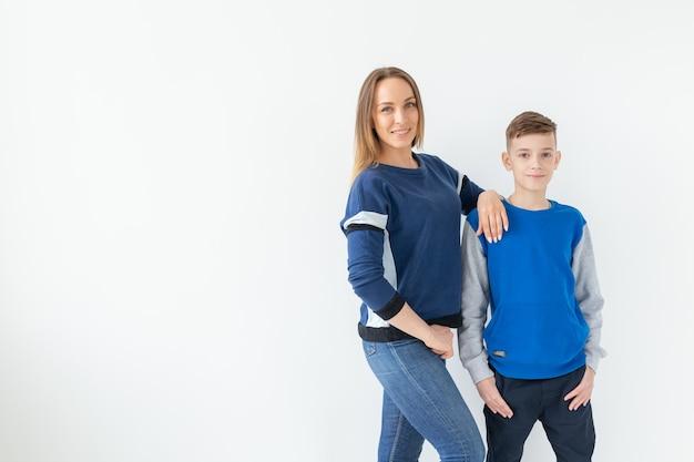 Концепция воспитания, семьи и родителей-одиночек - счастливая мать и сын-подросток смеются и обнимаются на белой стене с копией пространства.