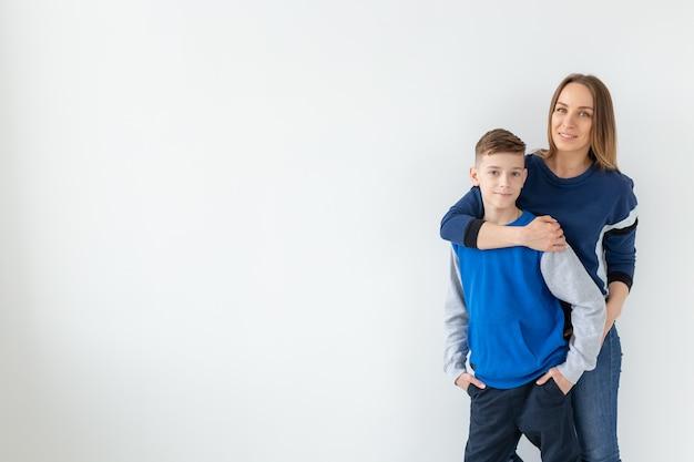Концепция воспитания, семьи и родителей-одиночек - счастливая мать и сын-подросток смеются и обнимаются