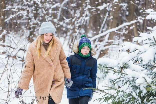 子育て、楽しさと季節の概念-冬に楽しんで雪遊びをしている幸せな母と息子