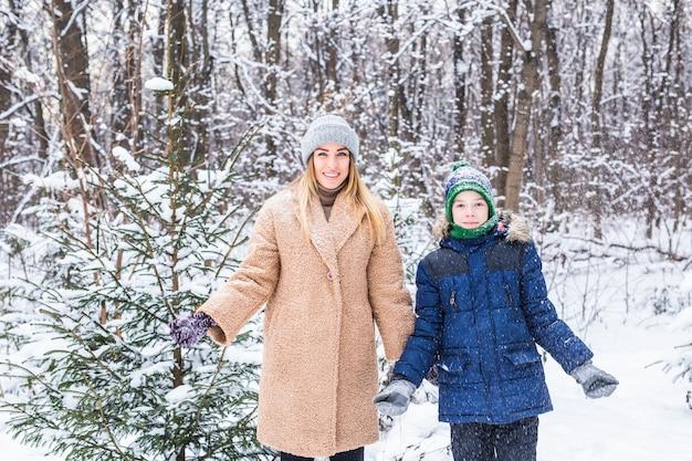 子育て、楽しさと季節のコンセプト-冬に楽しんで雪遊びをしている幸せな母と息子