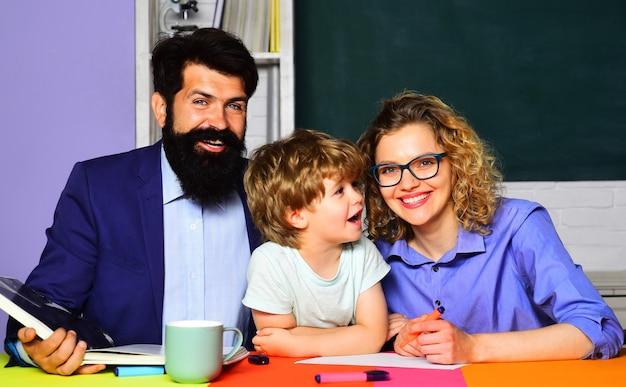 子育て。両親は息子が学校で宿題をするのを手伝います。小学生。メンタリング、教育、教育の概念。