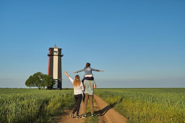 旅に出る両親と7歳の娘が灯台を見に行きます。緑の野原、青い空にある美しい古い灯台。ウクライナ、ヘルソン地域。幸せな家族は一緒に時間を過ごす