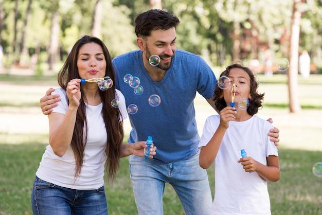 両親と公園で泡を吹いて素晴らしい時間を過ごしている少年