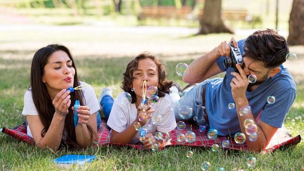 Родители и ребенок вместе пускают мыльные пузыри в парке