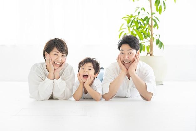 Родители и ребенок лежат и принимают одну и ту же позу