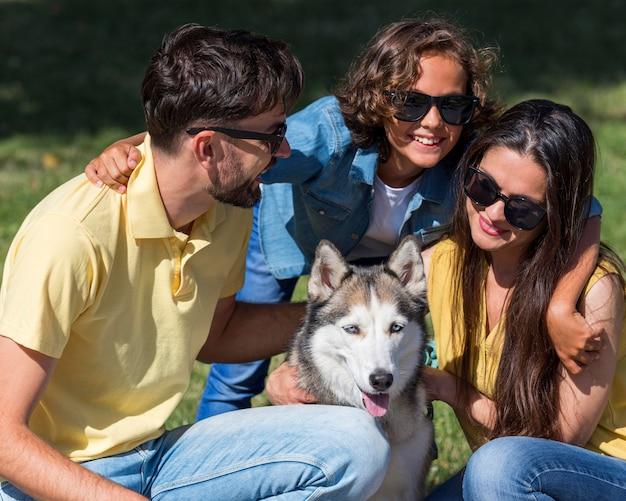 Родители и ребенок проводят время вместе с собакой в парке