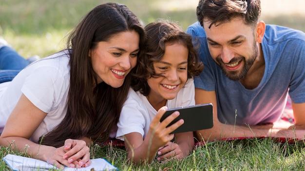 Родители и ребенок смотрят что-то на смартфоне в парке