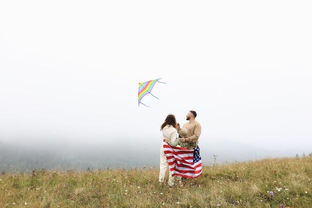 Родители и ребенок с американским флагом играют с красочным воздушным змеем. мать, отец и маленькая дочь вместе празднуют 4 июля на открытом воздухе в туманный день. день независимости сша концепции.