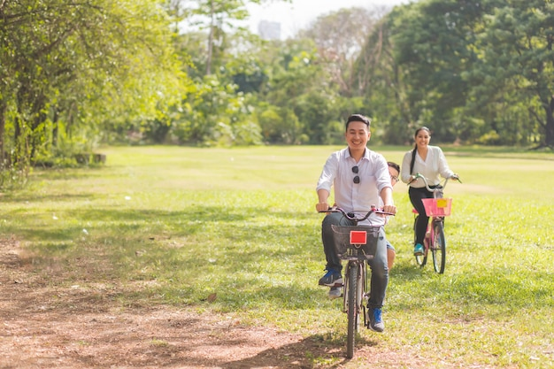 부모와 자녀는 아침에 웃는 얼굴로 정원에서 자전거를 타고 나무 배경에 만족합니다.