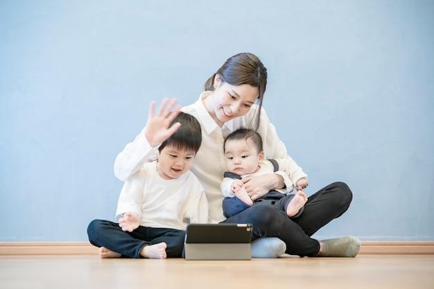 태블릿 pc를 사용하여 온라인 커뮤니케이션을 즐기는 부모와 자녀