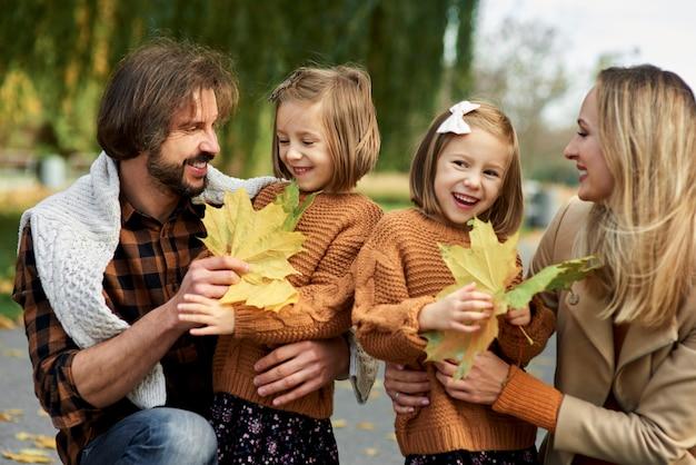 秋の季節に葉を摘む親子