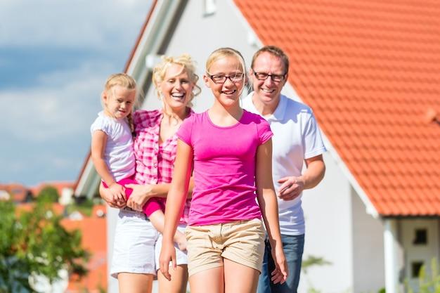 집 앞에 자랑스럽게 서있는 부모와 자녀
