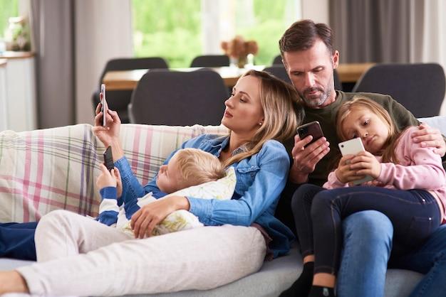 거실에서 휴대폰을 사용하는 부모와 자녀
